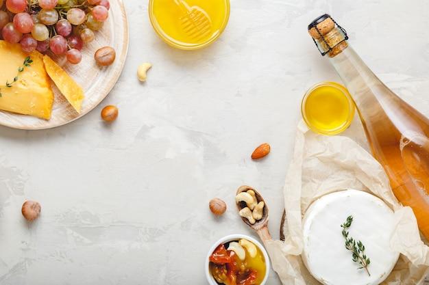 Rosa weinkomposition auf hellgrauem rustikalem betonhintergrund mit kopienraum. rahmen aus roséweinflaschen-käse-nüssen und rosa trauben, honig. camembert-käse, snacks in der weinbar.