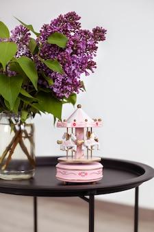 Rosa weinlese-musikkarussell und blumenstrauß der schönen frühlingsfliederblumen in der vase auf weinlese-couchtisch.