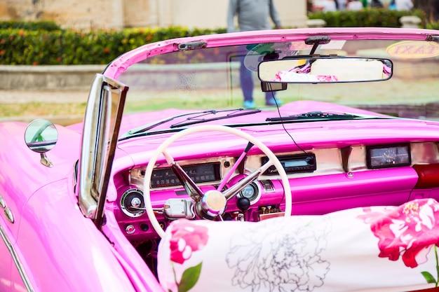 Rosa weinleseklassik-innenraum des amerikanischen autos, das auf der straße von altem havanna, kuba geparkt wird.