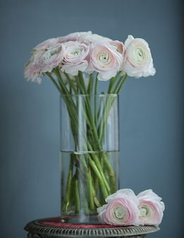 Rosa weiße blumen in der flasche auf dem tisch