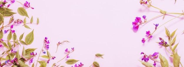 Rosa wilde blumen auf rosa papierhintergrund