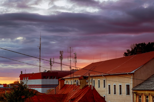 Rosa wolken des sonnenuntergangabendhimmels des dachs der häuser von uzhhorod-stadt, ukraine