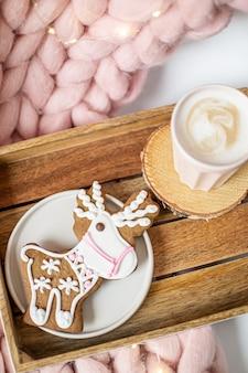 Rosa wolldecke aus pastellmerinowolle, lebkuchenhirsch und tasse mit cappuccino