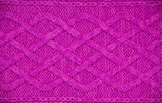 Rosa wollgarn gestrickte textur. handgestricktes zopfmuster mit 12 maschen. horizontal. nahaufnahme