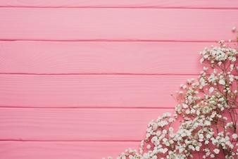 Rosafarbene hölzerne Hintergrund mit Blumenschmuck