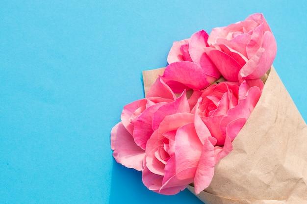 Rosafarbene rosen eingewickelt im packpapier