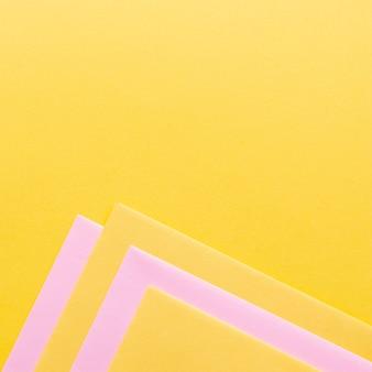 Rosafarbene und gelbe papierblätter mit exemplarplatz
