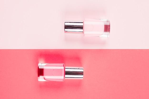 Rosafarbene und korallenrote nagellackflaschen gegen farbigen hintergrund