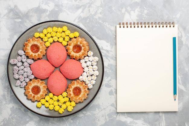 Rosafarbenen kuchen der draufsicht mit bonbons und keksen innerhalb der platte auf dem süßen hintergrund backen kuchen-keks-teekuchenplätzchen des weißen hintergrunds