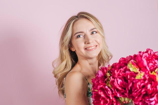 Rosafarbener blumenstrauß der schönen jungen frau gegen rosa hintergrund