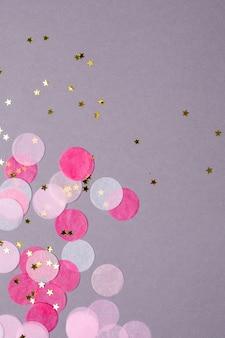 Rosafarbener confetti mit goldsternen auf grau mit copyspace