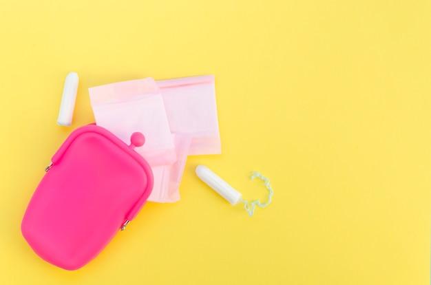 Rosafarbener geldbeutel mit eingewickelten damenbinden und tampons