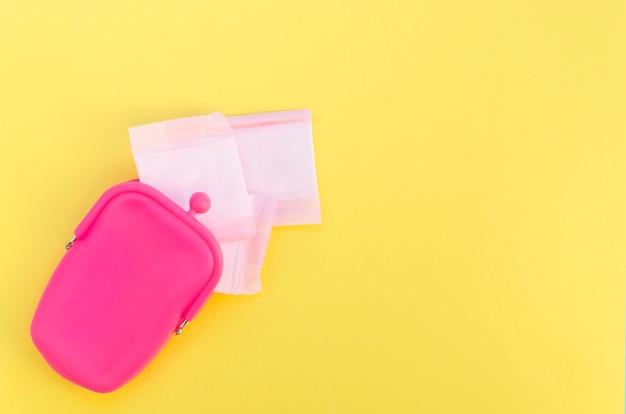 Rosafarbener geldbeutel mit eingewickelten damenbinden