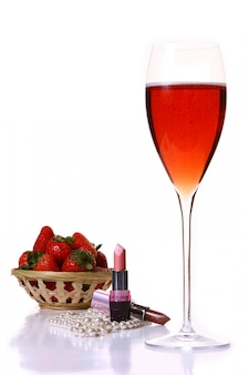 Rosafarbener lippenstift mit rotem champagle glas und erdbeere