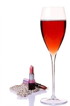 Rosafarbener lippenstift mit rotem champagle glas