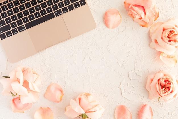 Rosagoldlaptop auf bürotischschreibtisch mit den rosenblumen und -blumenblättern lokalisiert auf weiß mit konkreter beschaffenheit