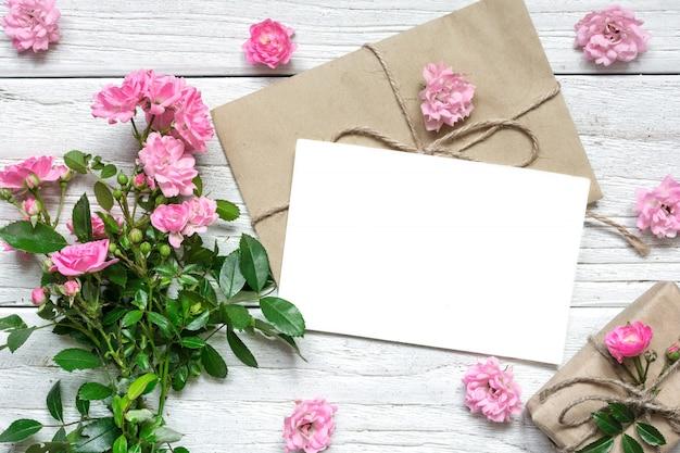 Rosarose blüht blumenstrauß mit leerer grußkarte und geschenkbox