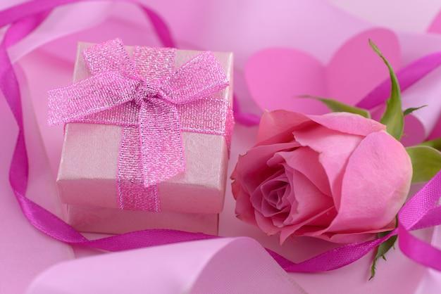 Rosarose und eine geschenkbox mit herzen, valentinstaghintergrund