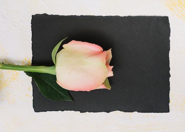 Rosarosenblume mit papier auf weißer tabelle