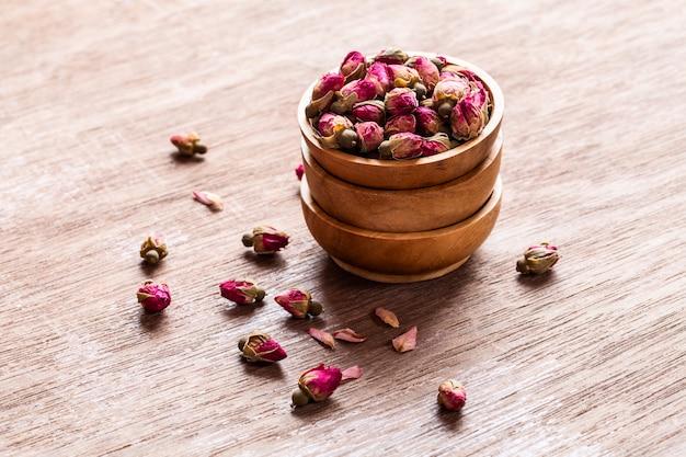 Rosarot getrocknete rosenknospen in den hölzernen schüsseln mit den blumenblättern