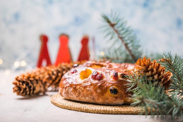 Rosca de reyes, spanischer drei-könige-kuchen, der am dreikönigstag auf einem grauen rustikalen tisch gegessen wurde
