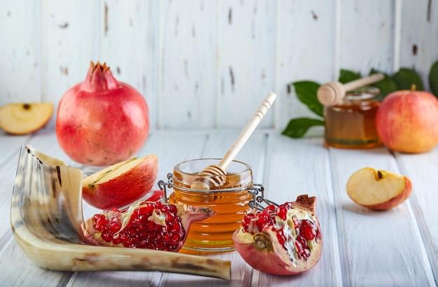 Rosch haschana - traditionelle symbole: honigglas und frische äpfel mit granatapfel und schofarhorn.