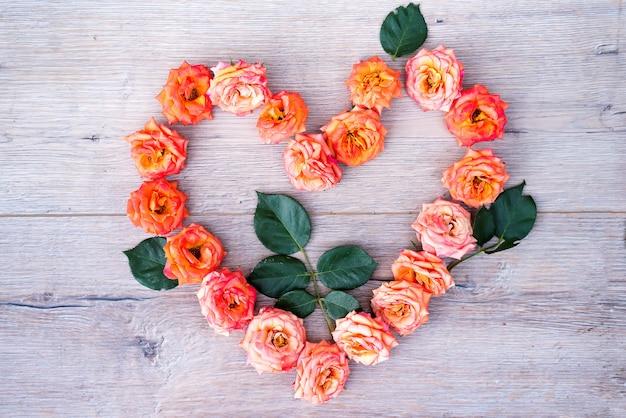 Rose blüht herzformrahmen auf hölzernem hintergrund. flache lage, draufsicht. valentinstag hintergrund.