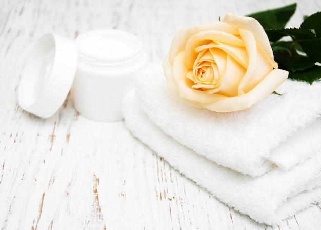 Rose mit feuchtigkeitscreme und handtüchern