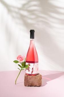 Rose weinflasche auf rotem stein und eine rosa rose gegen weiße wand mit sommerschatten. erfrischendes alkoholisches sommergetränk oder naturkonzept.