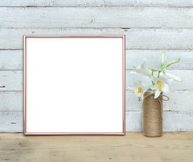 Roségold quadratisches rahmenmodell nahe einem blumenstrauß von lilien steht auf einem holztisch auf einem gemalten weißen hölzernen hintergrund. rustikaler stil, einfache schönheit. 3 rendern.
