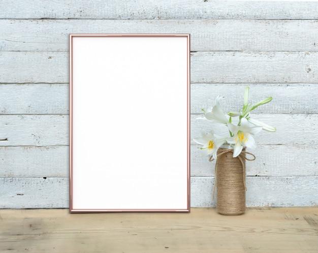 Roségold vertikales a4-rahmenmodell in der nähe eines blumenstraußes von lilien steht auf einem holztisch auf einem gemalten weißen hölzernen hintergrund. rustikaler stil, einfache schönheit. 3 rendern.