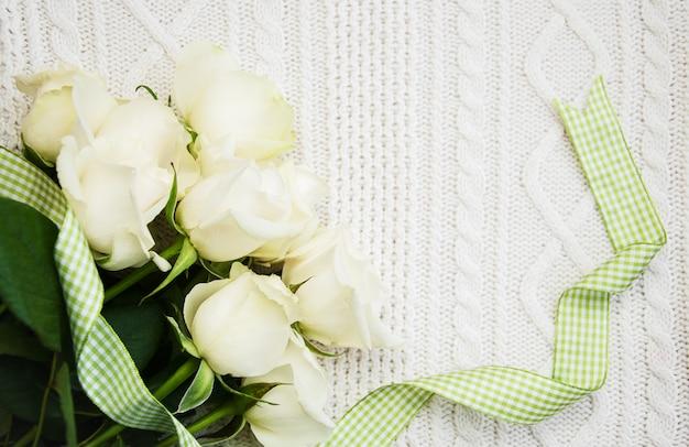 Rosen auf einem gestrickten weißen hintergrund