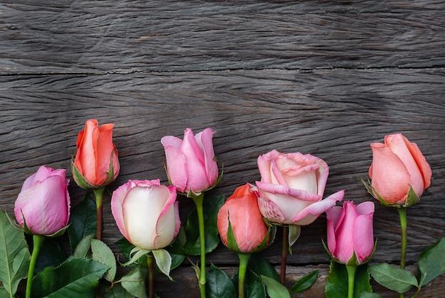 Rosen auf einem hölzernen hintergrund. unterschiedlich gefärbte blüten auf dunkler holzoberfläche