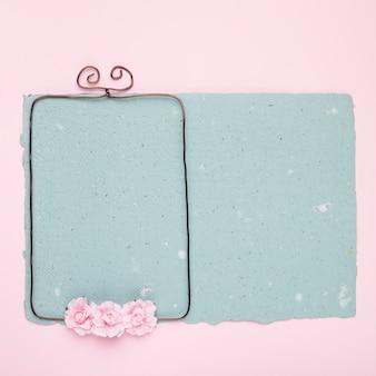 Rosen auf verdrahtetem rahmen über dem blauen papier auf rosa hintergrund