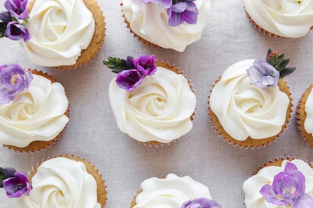 Rosen-blume, die vanillekleine kuchen mit purpurroten essbaren blumen bereift