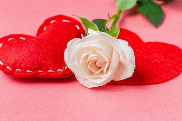 Rosen-blume mit herzen auf dem rosa hintergrund. valentinstag geschenk