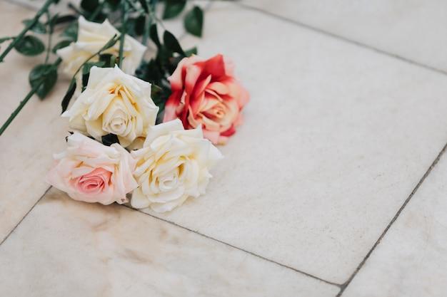 Rosen. blumen liegen auf einem granitboden.
