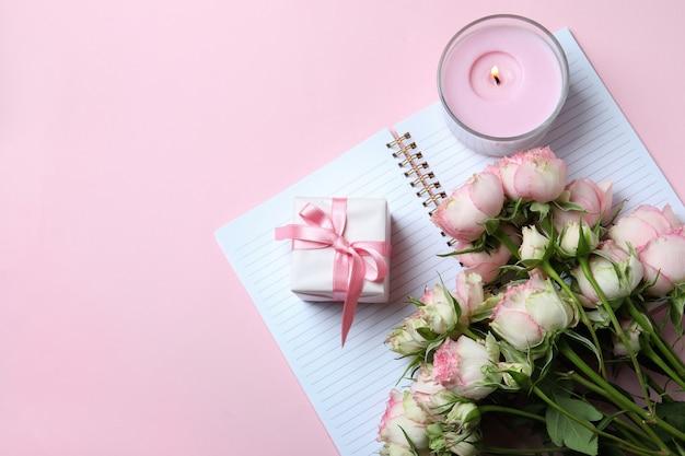 Rosen, geschenkbox, heft und kerze auf rosa hintergrund