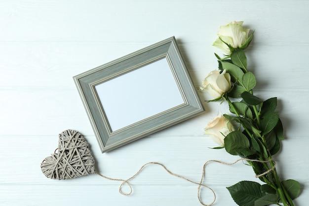 Rosen, herz und leerer rahmen auf weißem hölzernem hintergrund