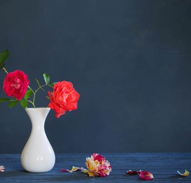 Rosen in der vase auf dunkelblauem hintergrund