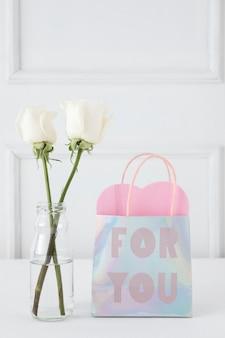 Rosen in der vase mit aufschrift auf papiertüte