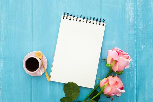 Rosen, kaffee und notizbuch