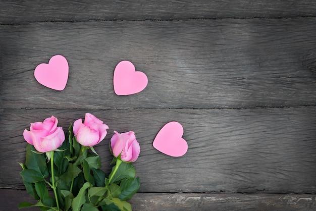 Rosen mit herzen auf einem hölzernen hintergrund. rosa blumen mit rosa herzen mit kopienraum auf dunklem hölzernem hintergrund