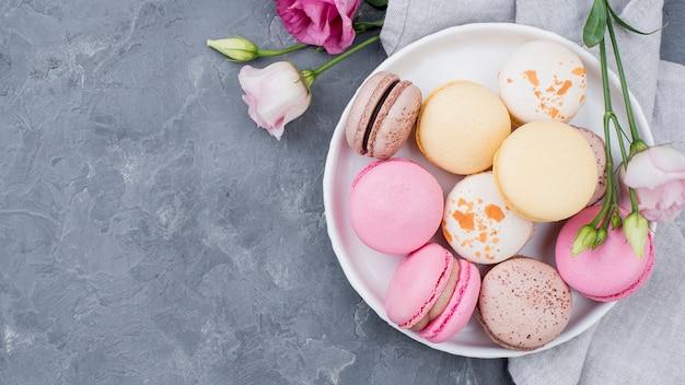 Rosen mit macarons auf teller mit kopierraum