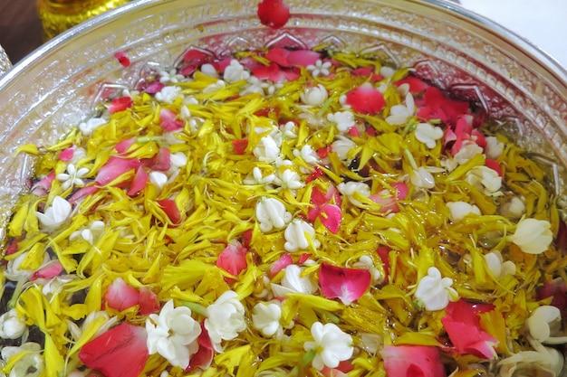 Rosen-, ringelblumen- und jasminblumenblatt in der silbernen schüssel auf blauem baumwollstoff, songkran-festival in thailand.
