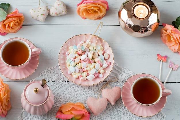 Rosen, tee in rosa tassen, herzen, süßigkeiten, dekor, zuckerdose, kerzenständer aus roségold