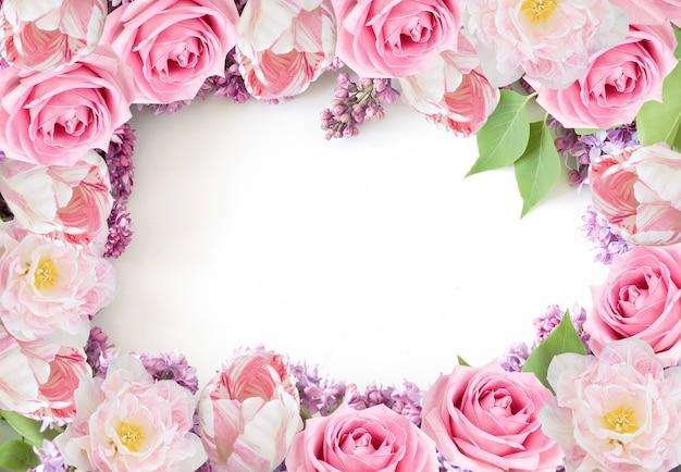 Rosen, tulpen und lila blumen rahmen auf weißem hintergrund für valentinstaggrußkarte ein