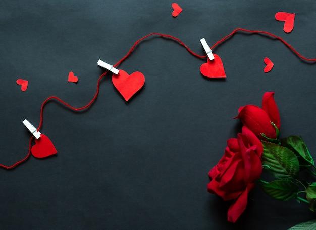 Rosen über schwarzem hintergrund und herzen gefangen durch schnur. prominente hintergrund. flache lage
