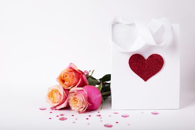 Rosen und geschenk in papierpackung mit rotem herzen