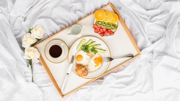 Rosen und gesundes frühstückstablett auf zerfallenem bett